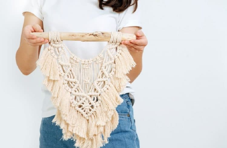 woman holding macrame wall hanging